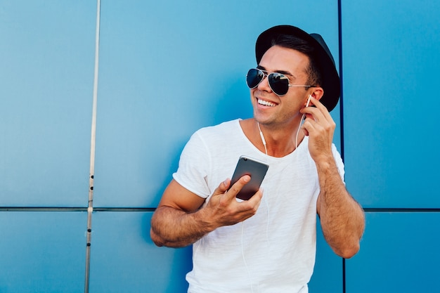 Outdoors photo of attractive guy in sunglasses listening to music in earphones Free Photo
