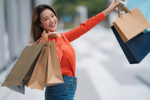 ショッピングバッグを押しながらモールで笑顔の幸せな女の屋外ポートレート Premium写真