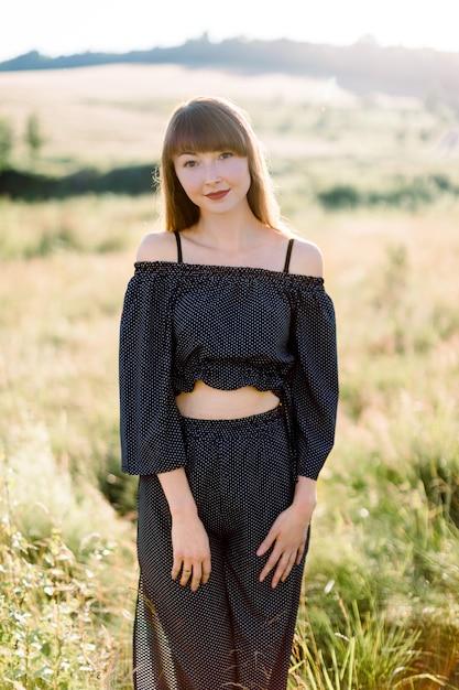 ファッショナブルな黒のスーツ、自然を楽しんで、晴れた日の美しい緑の夏のフィールドでカメラにポーズをとって若い魅力的な女の子の屋外の肖像画 Premium写真