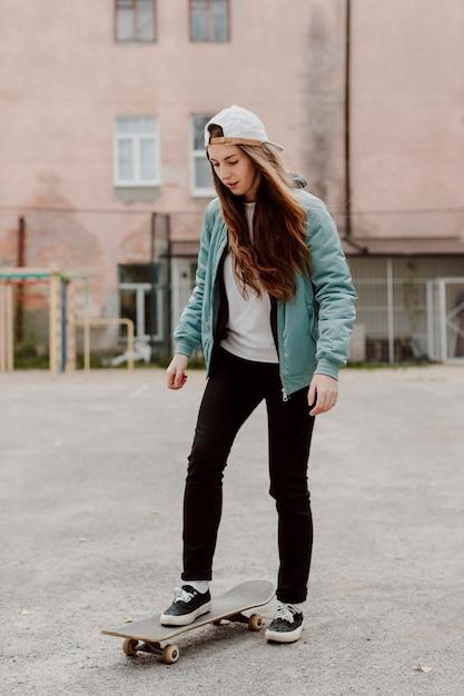 Ragazza pattinatrice all'aperto e il suo skateboard Foto Gratuite