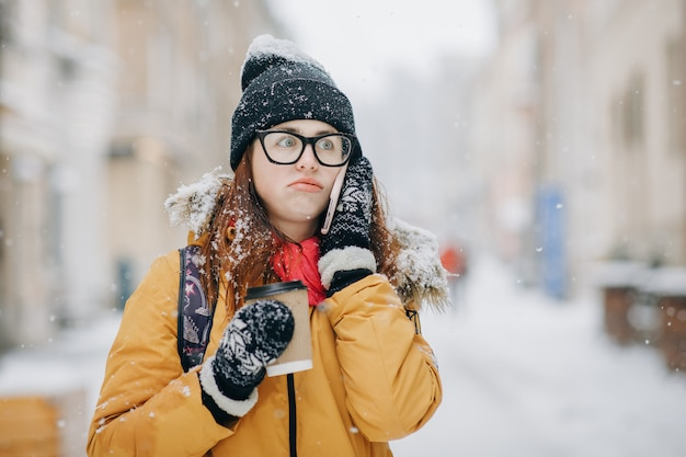 Outdoors winter portrait of beautiful teenage girl speaking on the phone Premium Photo
