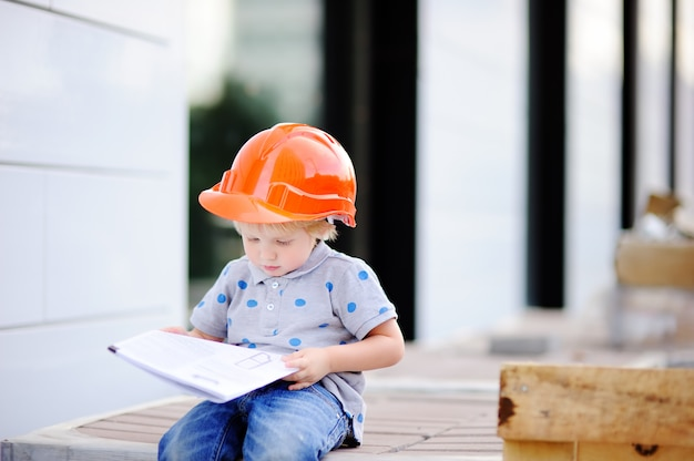 Портрет милого маленького строителя в защитных шлемах читая чертеж конструкции outdoors Premium Фотографии