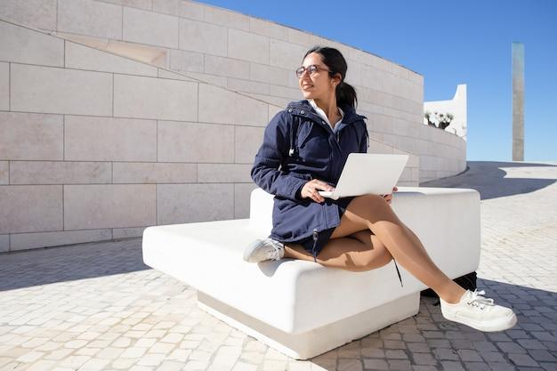 Счастливая студентка сидя на стенде и используя компьтер-книжку outdoors Бесплатные Фотографии