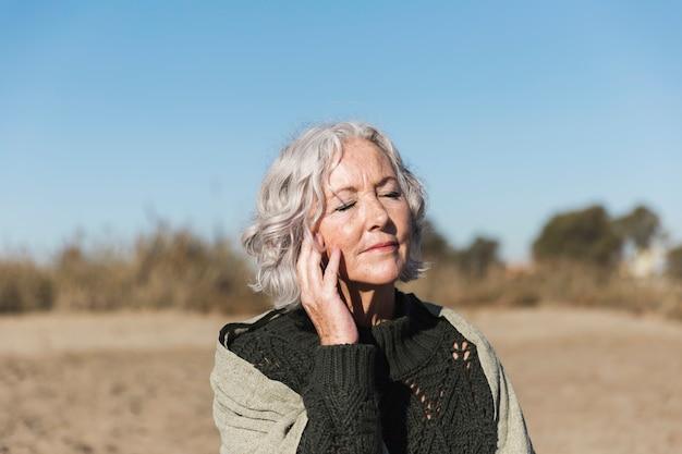 Красивая старшая женщина ослабляя outdoors Бесплатные Фотографии