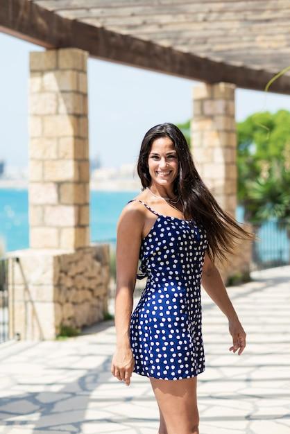 Красивая испанская женщина в голубом платье стоя outdoors пока смотрящ камеру Premium Фотографии
