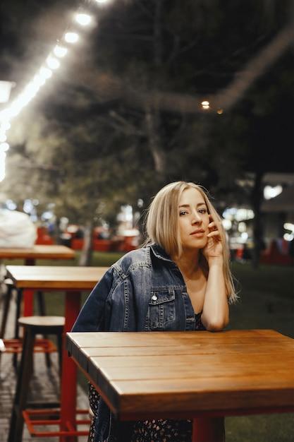 Привлекательная молодая кавказская белокурая девушка сидит около таблицы outdoors Бесплатные Фотографии