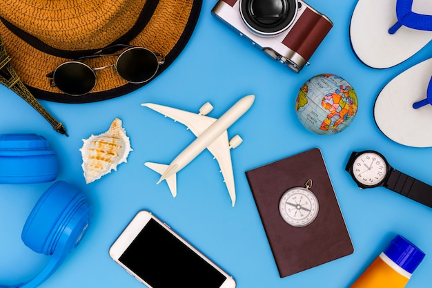 Outfit and accessories of traveler on blue background with copy space, travel concept, overhead view of traveler's accessories, essential vacation items, Premium Photo