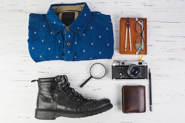 Outfit with travelling accessories on wooden table Free Photo