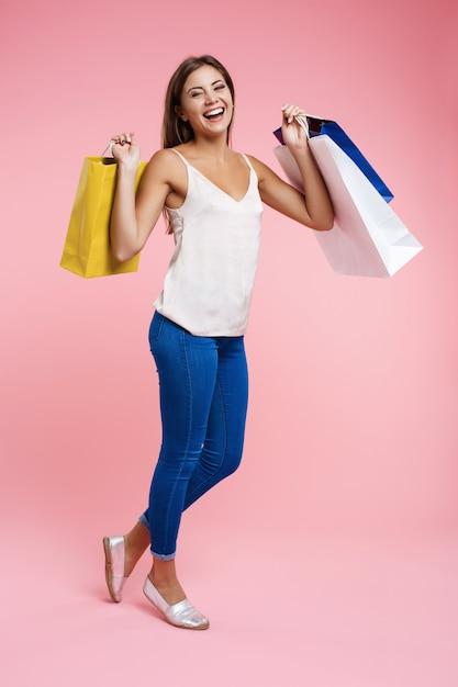 ショッピングバッグの束を保持しているトレンディな春outfutの女性 無料写真