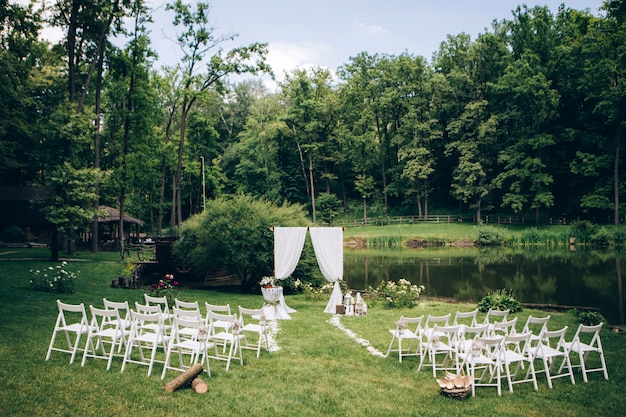 Outgoing wedding ceremony. decor studio. white wooden chairs on a green lawn. wedding festal arch. white armchairs for guests Premium Photo