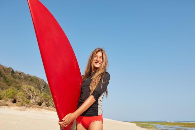 Наш снимок счастливой удивительной активной девушки с идеальной спортивной фигурой, здоровым образом жизни, бьющей по волнам доской для серфинга Бесплатные Фотографии