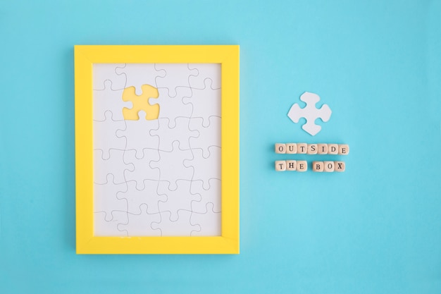 Outside the box blocks on yellow frame with white jigsaw puzzles Free Photo