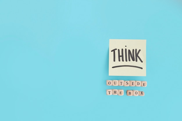 Outside the box text made with wooden blocks and think text on adhesive note Free Photo