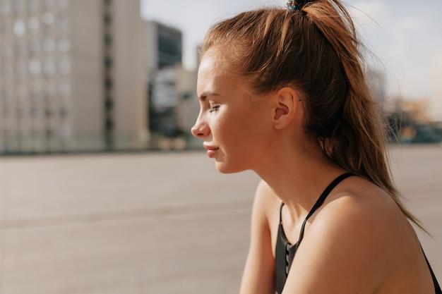 スポーツの制服を着た魅力的な若者の外の肖像画は、異例の間に休憩があります。日光の下で演習を行うスポーツ女性 無料写真