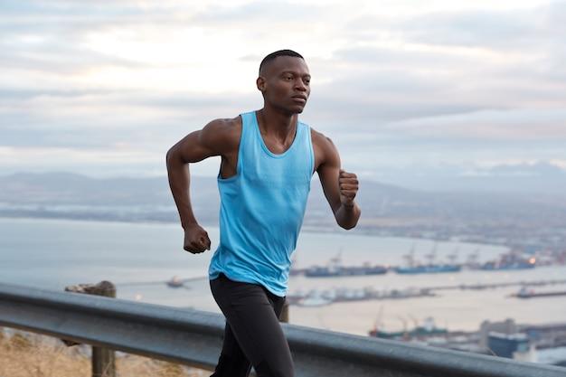 Colpo esterno di un uomo di fitness afroamericano fiducioso ha una sfida di raggiungimento degli obiettivi per raggiungere la destinazione senza interruzioni, lavora attivamente con le mani, vestito con abbigliamento sportivo, fa jogging su una bella vista della natura Foto Gratuite