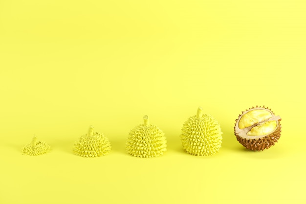Outstanding fresh cut ripe durian and slices of durian painted in yellow on yellow background Premium Photo