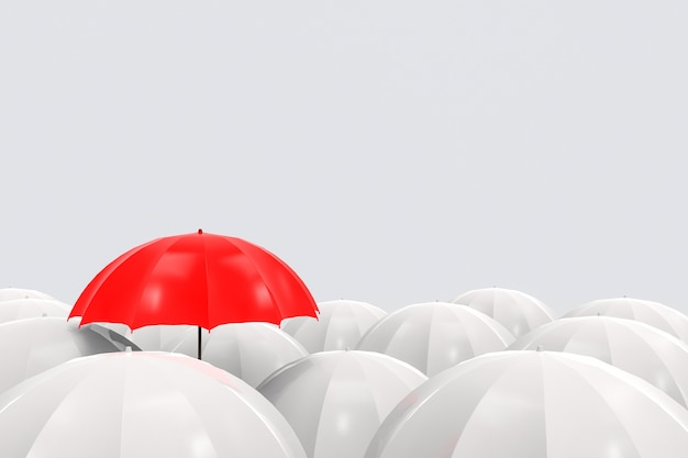 Outstanding one red umbrella is higher than the others on gray background. Premium Photo