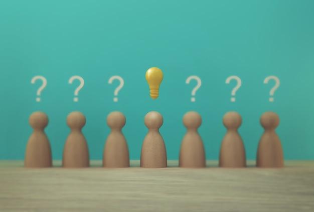 Модель выдающихся бумажных людей со значком лампочки и символом вопросительного знака Premium Фотографии