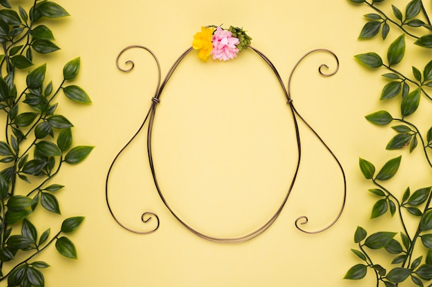 Oval shape frame with artificial rose on yellow wall with green leaves Free Photo