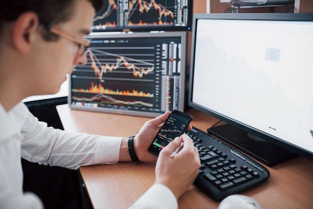 Через плечо виден и биржевой брокер, торгующий онлайн при принятии заказов по телефону. несколько компьютерных экранов с графиками и анализом данных в фоновом режиме Бесплатные Фотографии