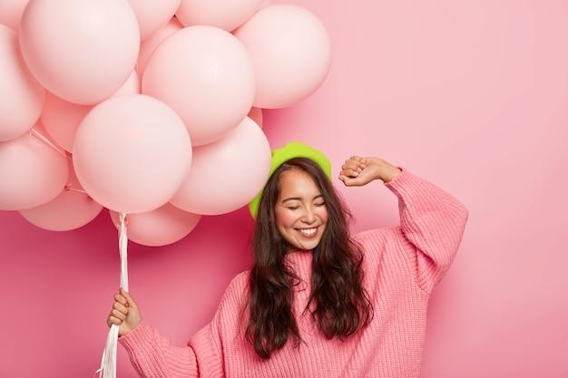 Сверхэмоциональная пугающая женщина с веселым выражением лица поднимает руку, танцует под музыку, веселится на вечеринке, держит воздушные шары, имеет хорошее настроение во время своего дня рождения Бесплатные Фотографии