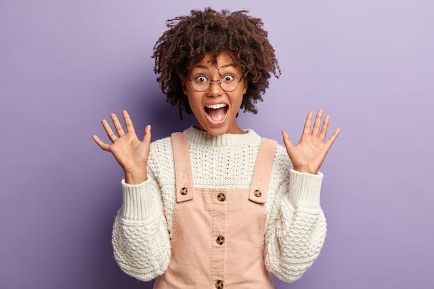 Giovani gesti femminili ipermotivi attivamente mentre condivide impressioni positive, grida di gioia, mostra i palmi delle mani, vestiti con tute alla moda, indossa occhiali rotondi, isolati su un muro viola. wow fico Foto Gratuite