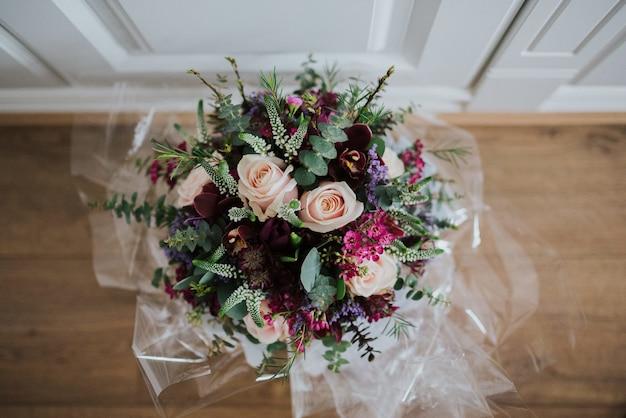 Colpo ambientale del primo piano di un mazzo di fiori di nozze su un pavimento di legno Foto Gratuite