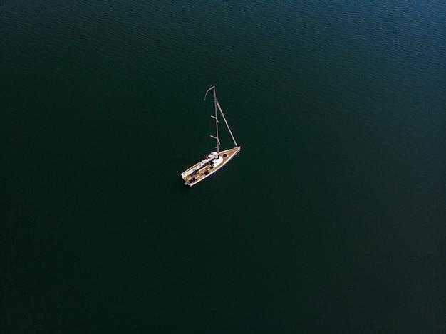 晴れた日に美しい湖でのセーリングボートのオーバーヘッドドローン写真 無料写真