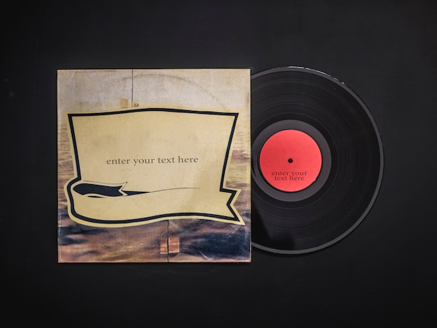 Overhead flat lay of blank vinyl record out from the cover  on black table Premium Photo