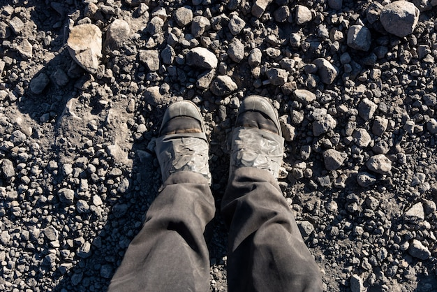 Overhead photo of feet on a background of brown soil . man feet Premium Photo