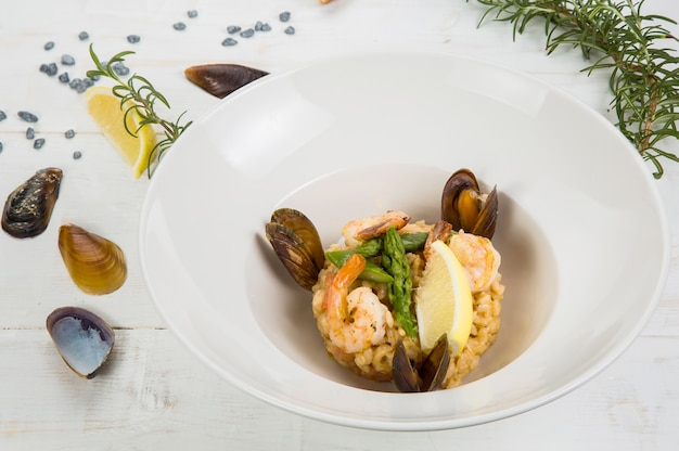 An overhead photo of a seafood risotto on teal textures, with a fork and a spoon, a glass of white wine, and a place for text Premium Photo