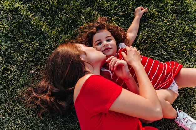 夏の日に一緒に冷やして幸せな家族のオーバーヘッドの肖像画。草の上に横たわっている間、彼女の小さな娘にキスする黒髪の女性の屋外ショット。 無料写真