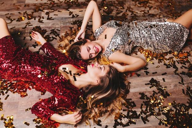 영감을 얻은 여성의 오버 헤드 초상화는 새해 파티 후 휴식하는 동안 귀여운 미소를 지닌 스파클 복장을 착용합니다. 무료 사진