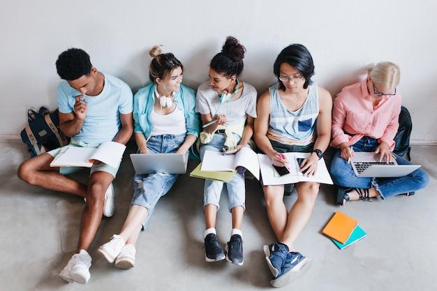대학에서 시험을 기다리는 국제 학생들의 오버 헤드 초상화. 숙제를 하 고 책과 노트북 바닥에 앉아 대학 동료의 그룹입니다. 무료 사진
