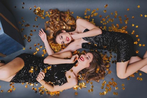 황금 색종이에 누워 두 즐거운 여자의 오버 헤드 초상화. 새 해 파티에서 갈색 머리 여동생과 함께 재미 검은 드레스에 긴 머리 아가씨. 무료 사진