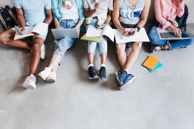 노트북 및 스마트 폰, 바닥에 함께 앉아 젊은 사람들의 오버 헤드 초상화. 무릎에 교과서를 들고 강의를 쓰는 학생들. 무료 사진