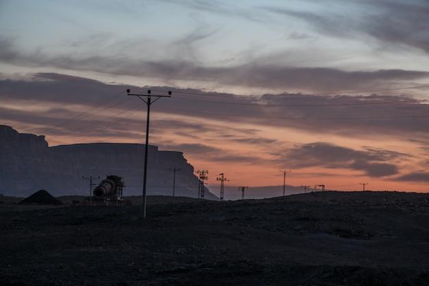 Linee elettriche aeree nella valle sotto il cielo nuvoloso al tramonto Foto Gratuite
