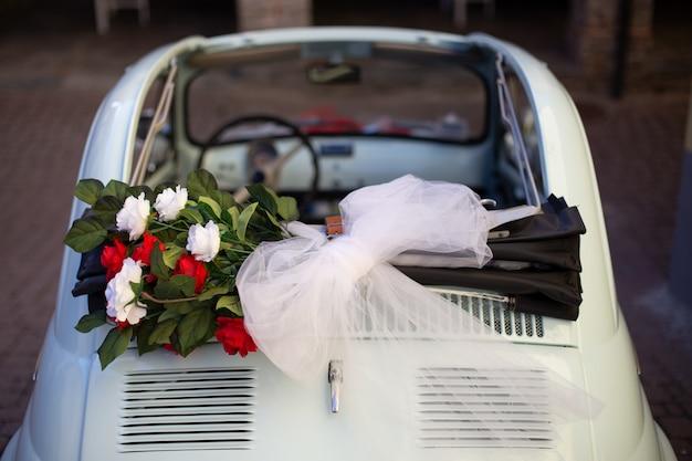 Scatto dall'alto di un mazzo di fiori posizionato nella parte superiore dell'auto con uno sfondo sfocato Foto Gratuite
