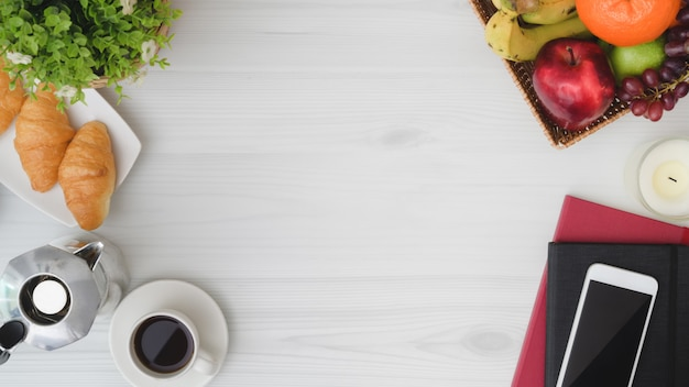 Overhead shot of  breakfast table with copy space, phone, notebook, fruit basket, croissant, coffee cup and moka pot Premium Photo