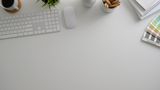 Overhead shot of minimal designer workspace with computer, office supplies, colour swatch  and copy space Premium Photo