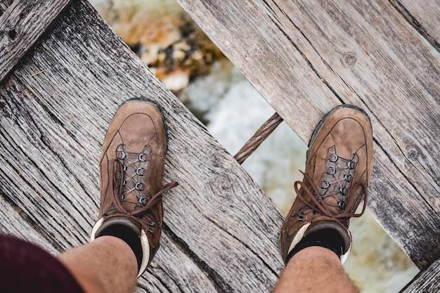 ハイキングシューズを身に着けている木製の橋の上に立っている男性の足のオーバーヘッドショット 無料写真
