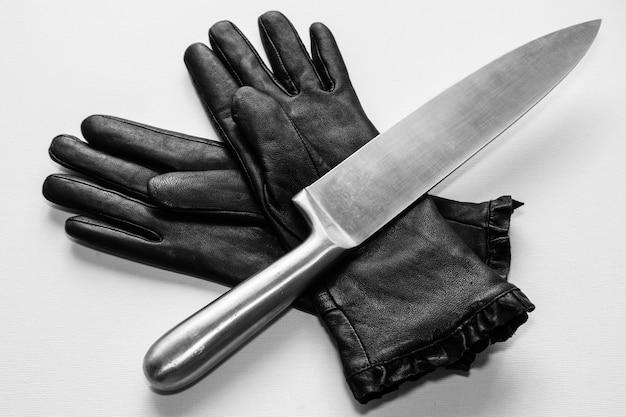白い表面に黒い手袋の上の金属ナイフのオーバーヘッドショット 無料写真
