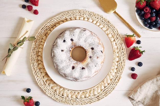 白いテーブルの上の果物と粉とリングケーキのオーバーヘッドショット 無料写真