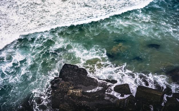 岩の上をはねかける岩と水域の近くの岩だらけの海岸のオーバーヘッドショット 無料写真