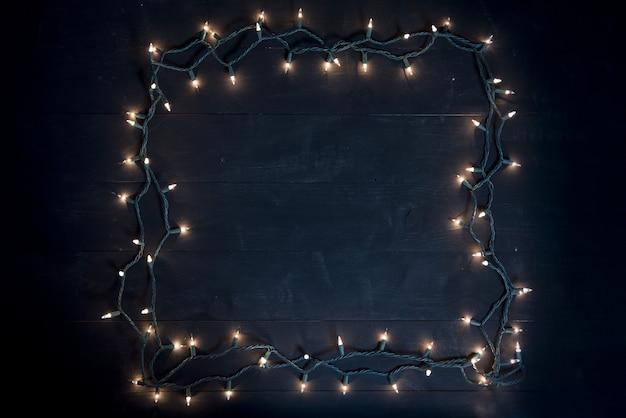 나무 표면에 크리스마스 불빛으로 만든 사각형의 오버 헤드 샷 무료 사진