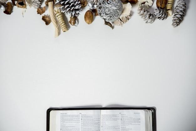 Верхний снимок открытой библии на белой поверхности с шишками и орнаментом на вершине Бесплатные Фотографии