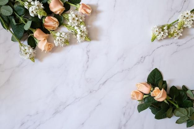 白い大理石の表面に緑の葉と白い小さな花と庭のバラのオーバーヘッドショット 無料写真