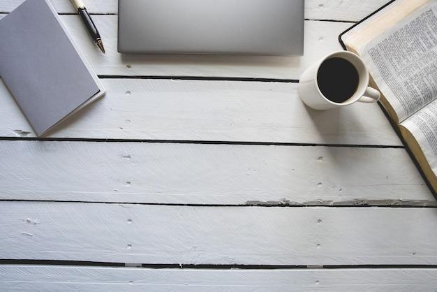 Верхний снимок белой деревянной поверхности с ноутбуком, библией, кофе и блокнотом с ручкой сверху Бесплатные Фотографии