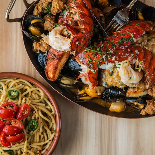 Overhead shot of pasta near a pan of fried lobster and meat with oysters on a wooden surface Free Photo