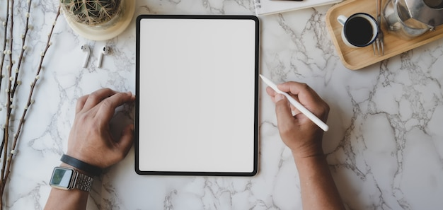 Overhead shot of stylish workspace with blank screen tablet and office supplies on marble desk Premium Photo